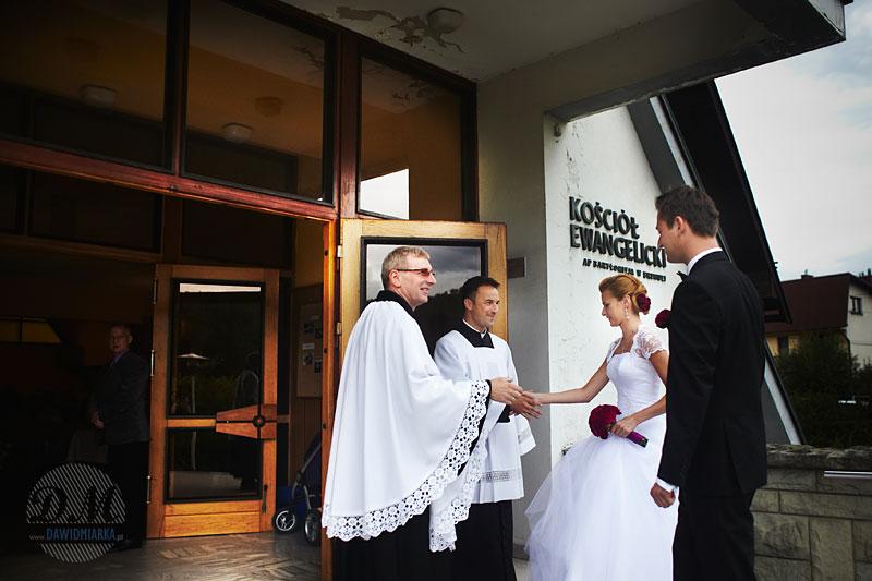 Księża ewangelicki i katolicki witają Młodą Parę przed kościołem