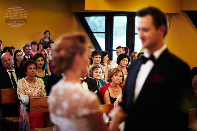 Fotografia przedstawia moment składania przysięgi małżeńskiej przez nowożeńców