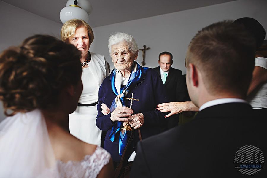 Babcia z krzyżem przy blogosławieństwie.  Tani Fotograf Nowy Sącz.