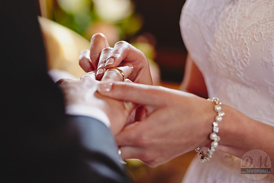 Założenie obrączek podczas ślubu na fotografii ślubnej w trakcie zaprzysiężenia.