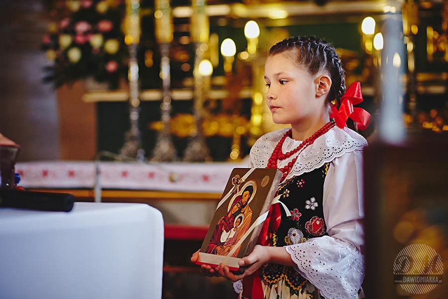 Młoda dziewczynka trzymajkąca obraz świętej rodziny. Fotograf Stary Sącz.