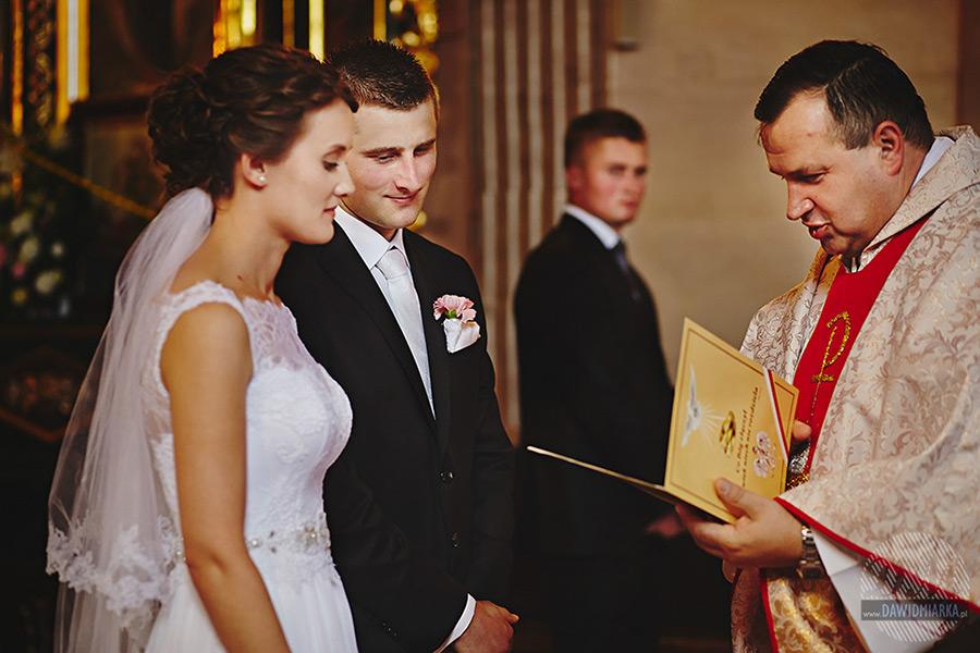 Przekazanie dokumentów przez księdza do państwa młodych na ślubie podczas mszy.