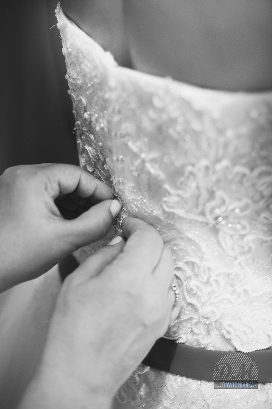 Zdjęcie z przygotowań panny młodej. Matka Panny młodej spina suknie ślubną.