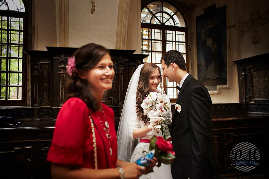 Czułe słówka Pana młodego do Panny młodej na chwilę przed ślubem w Bazylice Dominikanów w Krakowie. Fotografia ślubna Kraków.