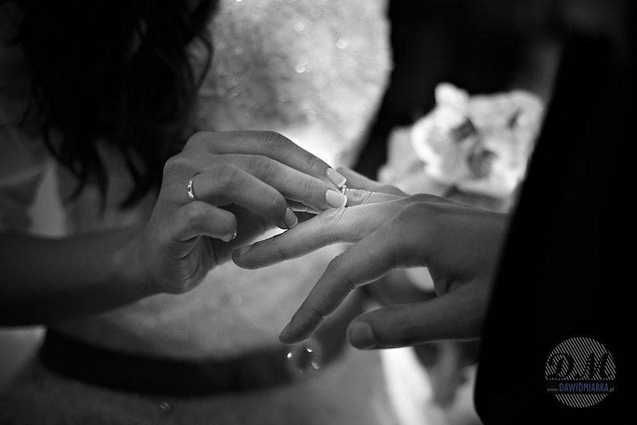 Panna młoda nakładająca obrączkę Panu młodemu na fotografii ślubnej z Krakowa.