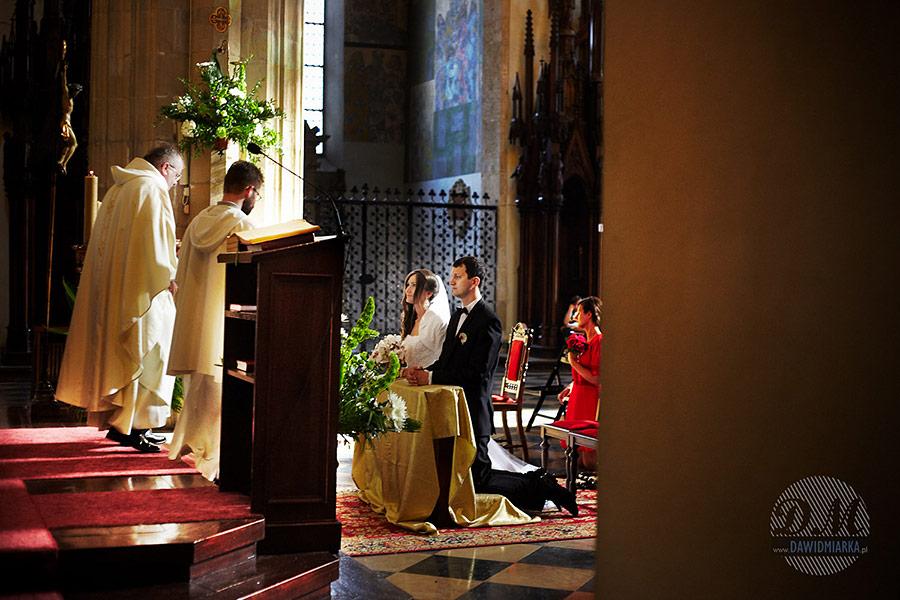 Ten fotograf na ślub w Krakowie. Fajne zdjęcie ślubne. Para młoda klęcząca przed ołtarzem.