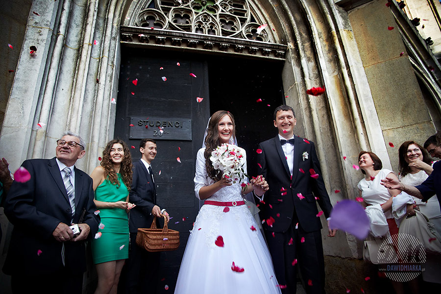 Para młoda przy wyjściu z kościoła Dominikanów. ze swojego ślubu. Kwiaty. Fotograf ślubny Kraków.