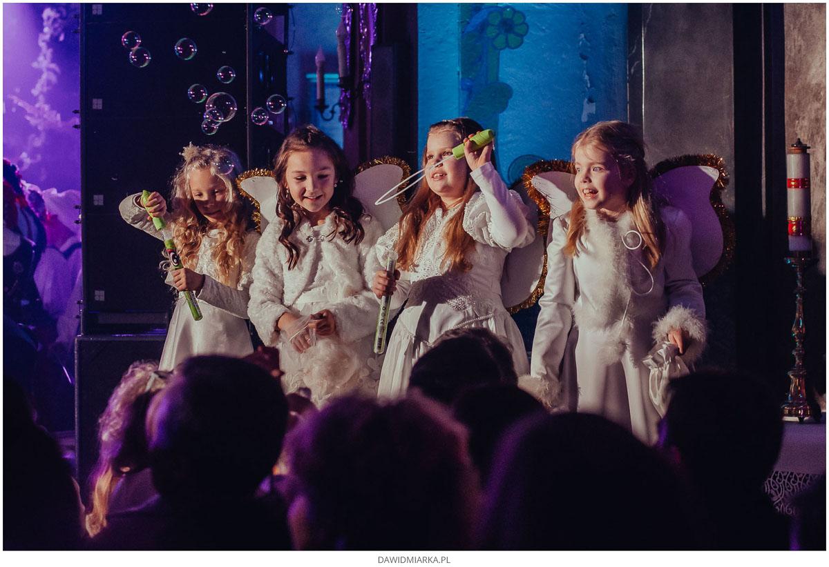 Dzieci aniołki puszczają bańki w kościele na koncercie.